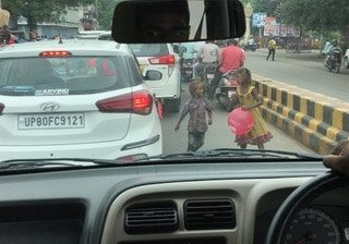 Children selling balloons to drivers at a busy intersection in Kolkata